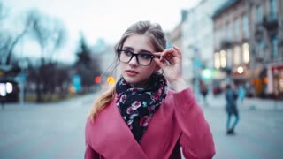 Sexy woman moving right towards the camera, looking around, touching her glasses. Trendy look. Urban settings on the background. Perfect runaway. Being self-confident, happy.