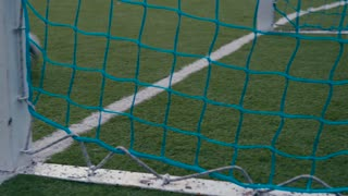 Shooting from behind the net, the soccer ball flies into a gate. Failing the match, losing the game. Winning the match, victory. Professional game.