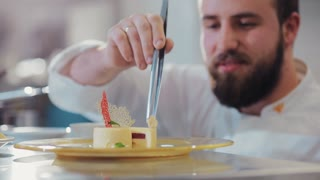 Smiling bearded confectioner decorates the vanilla mousse pastry dessert, checks the result of his work. Professionalism, cheerful mood. Career ladder, motivation. European cuisine, delicious dessert
