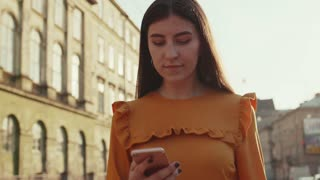 Smiling young woman in trendy blouse walks down the busy city street, looks at het phone, texts messages. Positive mood, cheerful emotions. Being online, browsing the internet. Female portrait, sun