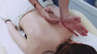 Strong male hands of professional masseuse massaging woman's back. Relaxation time, healthy lifestyle. Spine therapy, spa activities. Calm down.