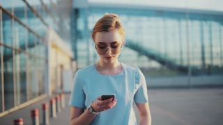 Stunning business woman walking down the deserted street and using her smartphone. No people around. Trendy look, cheerful mood, luxury lifestyle.