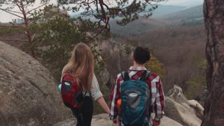 Stylish European backpackers reach the summit top, they observe amazing view of mountains and forest, smiling and holding their hands. Romantic atmosphere, couple goals. Extreme adventure.
