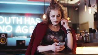 Stylish hipster girl with red lips using her phone in a cozy café, gets the message, looks disappointed, texts back. Modern life, social networks. Outdoor activity. Female portrait, light makeup.