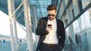 Stylish young bearded man walks down the airport terminal, uses his phone, surprises with the message, takes off the sunglasses, smiles. Cheerful mood, being happy.