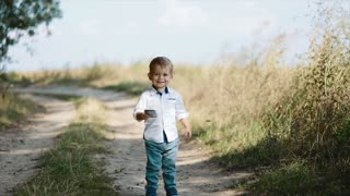 Sweet baby-boy as a young businessman holds the smartphone, runs towards the camera and smiles happily. Modern kids, social networks, kid blogger. Happy childhood