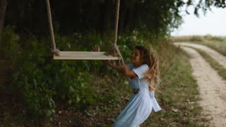 Sweet little girl in a white beautiful dress hides behind the wooden swing seat from her brother, then he catches her up, but she runs away, the boy chases his sister. Happy together
