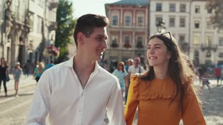 Sweet young people in love walk down the historical city center, holding their hands, laughing, a man kisses his girlfriend in cheek. Couple goals, true feeling, joy of life. Love story