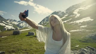 Taking selfie, making peace on the mountains hill, bright sunshine.