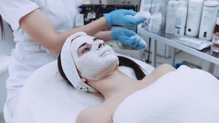 The cosmetologist cleans off beautiful woman's face from the beauty mask. Cosmetic procedure, skincare. Taking care of yourself. Female activities, facial care.