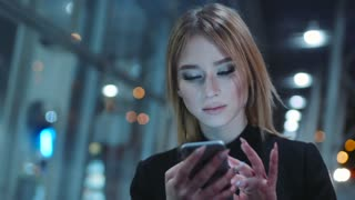 The girl in a good mood in the dark clothes is on the evening street. She is near the business center. The girl is concentrated texting with someone in the telephone.