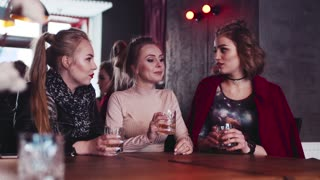 Three gorgeous women party hard with alcohol cocktails. Having fun with a true friends, drinking toast to friendship. Young and beautiful, happy memories. Enjoy life.
