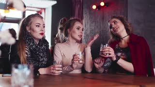 Three old sexy friends having a trustful conversation in the bar, holding glasses of alcohol cocktails. Fashionable look, happy to meet each other. Friends time.