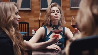 Three seductive women in cocktail dresses cheering, drinking red wine and having a conversation in an old-fashioned restaurant. Friends forever, being happy together.