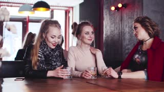 Three stylish housewives having a rest in a bar, drinking cocktails and talking to each other, joking. Happy time, amazing atmosphere. Being happy together, true friends.