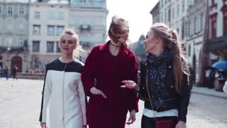 Three young stylish women walking, talking, laughing in the city-center. Fashionable look, amazing red coat. True friendship. Leisure time. Urban architecture. Sunny weather.
