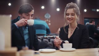 Two young lovers having a lively conversation and laughing on a date drinking coffee in a modern restaurant.