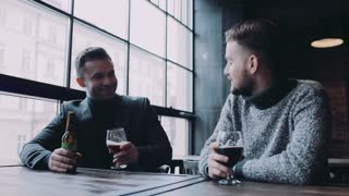 Two young man having mug of lager beer in a deserted pub, they toast and praise the taste. Little party, alcoholic relaxation. Friendship forever, celebration.