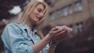 Windy weather, blonde girl in jeans jacket is holding pink flower petals in her hands, then blows away it. Cute smile, female portrait. Spring time, evening. Outside shooting, close up view, rotation.