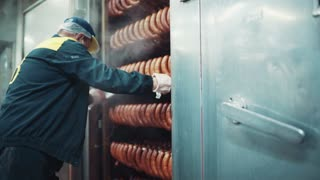 Workers of the food factory pulling the rack with the hanging smoked sausages out of the automatic smoking machine. Food industry, workplace. Delicious, junk food. Manufacturing process.