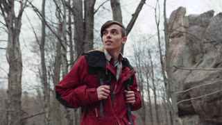 Young backpacker walking through the deserted forest, happily smiling and observing the scenery. Autumn season, fallen leaves around. High rocks. Active lifestyle. Slow motion, camera stabilizer shot
