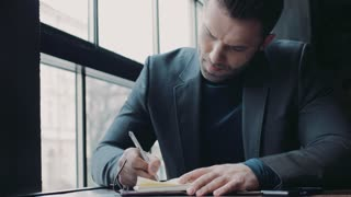 Young bearded man in a formal outfit writing down the ideas on the paper in a café. Being the boss. Successful lifestyle. Café interior on the background. Male portrait.