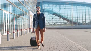 Young bearded man in sunglasses having a business trip, pulling the suitcase to the airport. Active lifestyle, having vacation. Modern airport on the background.
