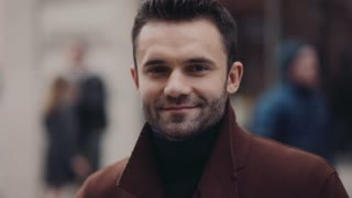 Young bearded man stands in the crowded street and smiles towards the camera. Stylish outfit, modern male fashion. Active lifestyle, bachelor.