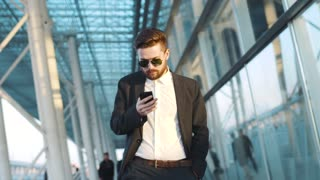 Young bearded man walks through the airport terminal, notices smth on his phone, takes off the sunglasses in surprise, continues walking.