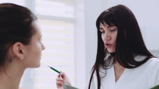 Young beautiful brunette cosmetologist, doctor gives the advice to her patient in the cabinet. Medical treatment, facial therapy, healthy lifestyle. Enjoying the job, natural beauty.