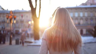 Young beautiful girl walks down the busy street with her hair loose, turns around laughing to the camera and then continues her walk.