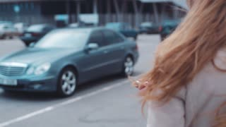 Young beautiful lady comes to her brand-new modern car, unlocks it, sits and starts driving home away from a modern building.