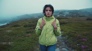 Young beautiful woman with a backpack, scared look, walks down the stoned path. Foggy weather, no people around. Adventure, active lifestyle, hiking Slow motion camera stabilizer shot, female portrait