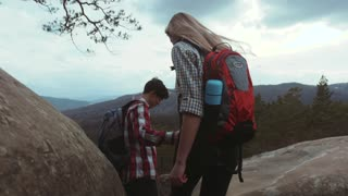 Young couple climbing the rocky hills, stylish young man with a backpack gives a hand to his beautiful girlfriend with a long hair, while moving to the top of the mountain.