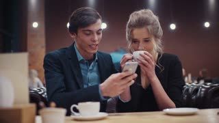 Young couple dating in café. A guy with a smartphone in his hand and a girl who is drinking coffee have a lively conversation.