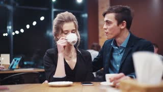 Young couple talking freely, laughing happily, kissing and enjoying each other, then looking at phone's screen in front of them on the table while on a date.