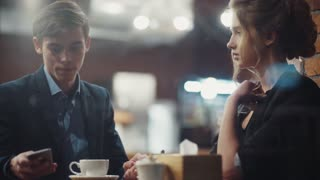 Young couple talking lively, drinking coffee having a date in a nice new modern café in city center.