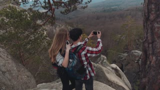 Young European brunette man and blonde girl having a great time together on the top of the mountain, taking photos of amazing scenery down the hill. Stormy weather, romantic date.