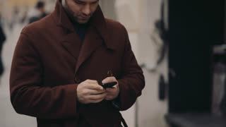 Young handsome man in a fashionable coat standing in the city center and using his phone for texting the message. Modern lifestyle, technologies, social networks.