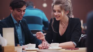 Young happy couple dating. The girl tasting guy's coffee and the guy laughing kiss each other.