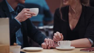 Young happy couple talking freely and drinking coffee on a date in a new expensive restaurant.