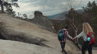 Young hikers walking on the high mountain hill in a stormy, windy weather. He helps a girl to climb up, holding hands. Dangerous extreme adventure. Love story. Wonderful scenery.