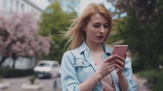 Young lady in a jeans jacket, is using her phone in the city. Urban buildings, cars on the background, windy weather. Cool atmosphere. Female portrait, no people around. Outside shooting.