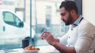 Young man in a café, taking several photos of his breakfast coffee and croissants to post it online. Modern lifestyle, blogger. Technologies.