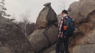 Young man in a checkered shirt stands on the top of the big rock and takes several shots of amazing scenery. No people around. Adventure, extreme hiking, having a rest.