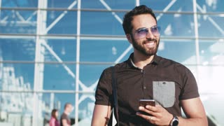 Young man positively looking around and using his smartphone while coming out of the modern glassy building. Stylish look, cheerful mood. Being happy, traveling time.