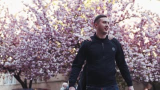 Young man walking down the street, his beloved girl runs and surprisingly jumps on him, they are laughing happily. Love story, true emotions, cuteness. Cherry flowering tree on the background