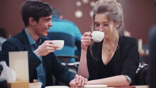 Young nice couple holding hands having a lively conversation laughing cheerfully having a date in a modern urban café.