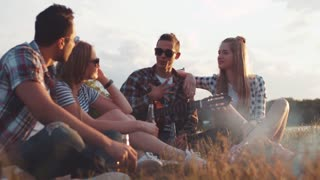 Young people in stylish sunglasses having a picninc, sitting by the campfire and talking actively to each other, laughing and drinking beer. One young guy holds the guitar.