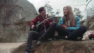 Young people sitting on the rock and singing a song, young man playing the guitar, and charming blonde girl drinking hot tea, smiling. Enjoying each other. Forever in love. Big rocks on the background